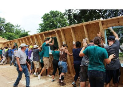 giving back conrad property management inc. people raising a wall